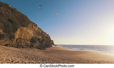 Paragliders Fly Over the Ocean Beach