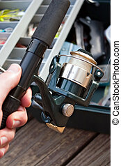 Fishing Gear - A hand holding a fishermans rod reel and...
