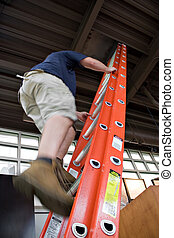 Man Climbing a Ladder - A young worker climbing up a ladder...