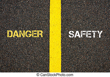 Antonym concept of DANGER versus SAFETY written over tarmac,...