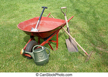Wheelbarrow and Gardening Equipment - A red wheelbarrow on...