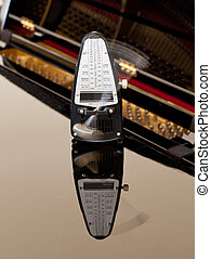Metronome ticking and reflected on piano - Metronome and...