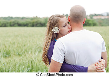 Loving couple standing in the field woman embracing her...