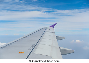 airplane wing with cloudy sky