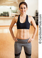 Happy girl with toned abs in a gym - Beautiful and strong...