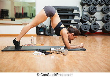 Exercising her abs in a butt up position - Profile view of...