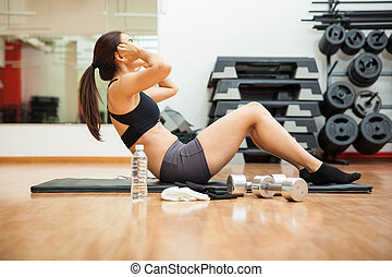 Strong woman doing crunches at the gym - Profile view of a...