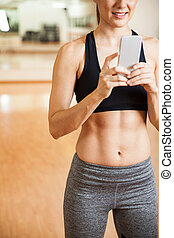 Woman with abs using a smartphone at the gym - Closeup of...