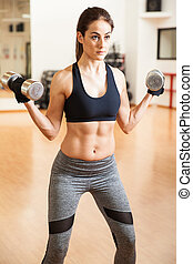 Woman with abs lifting weights at the gym - Fit and strong...