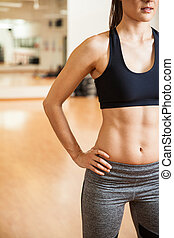 Strong woman with toned abs at a gym - Closeup of half of...