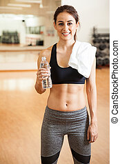Woman with toned abs taking a water break - Portrait of a...