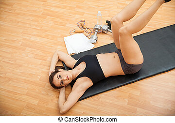 Woman strenghtening her abs at the gym - Cute young brunette...