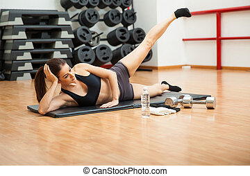 Young woman doing side crunches at the gym - Cute athletic...