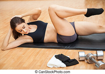 Woman doing crossover crunches in a gym - Athletic young...