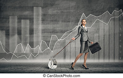 Woman controlling time - Elegant businesswoman with suitcase...