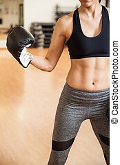 Strong woman with boxing gloves in a gym - Closeup of the...
