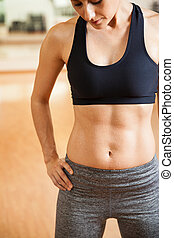 Closeup of a woman with sweaty abs - Close crop of an...