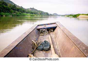 Wooden longtail boat head out into the Mekong River,...