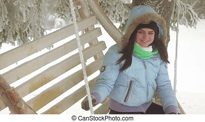 Girl on swing in forest - On wooden swing girl sits in snowy...