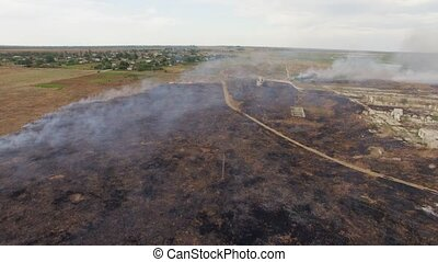 Dry Field Burning Near Settlement - AERAIL VIEW Flying shot...