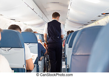 Steward on the airplane. - Interior of airplane with...