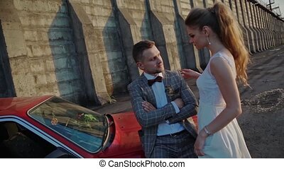 Newlyweds on the background of a dam and a red car