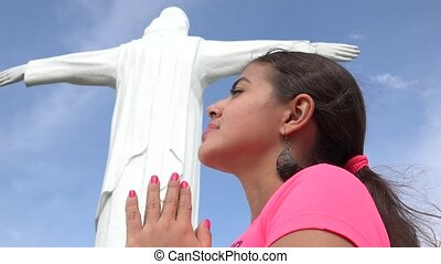 Woman Praying At Religious Statue