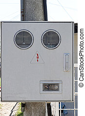 Electricity meter box with round windows at pole