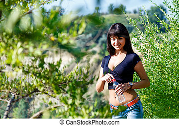 smiling girl with bottle of water between green trees  in summer