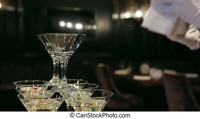 Waiter pours champagne in glass tower of champagne coctail restaurant