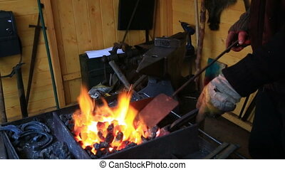 Traditional farrier working with fire in smith -...