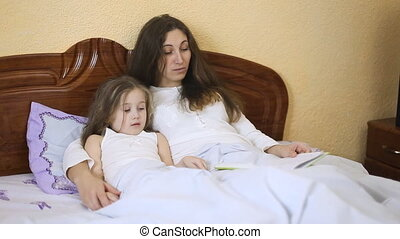 Mother daughter reading a fairy tale - mom reads a story to...