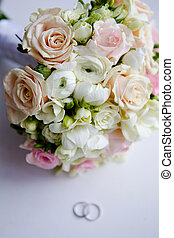 wedding bouquet on the table with rings - wedding with...