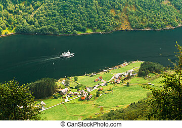 Ship sailing between fjords Village near Sognefjord fjord in...