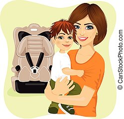 young mother holding little boy next to baby car seat