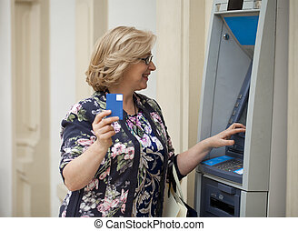 Mature blonde woman counting money near ATM - Mature blonde...