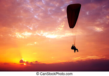 Flight of paraplane above Mediterranean sea on sunset