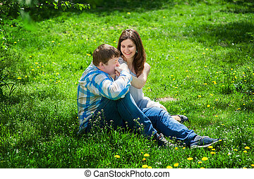 Man with a woman sitting on the grass and he kisses her...