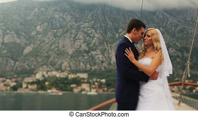 Beautiful wedding couple holding on the yacht with the...