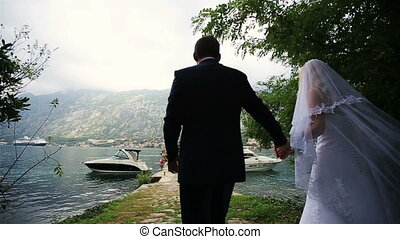 Wedding couple walking on the romantic bertn in Montenegro,...