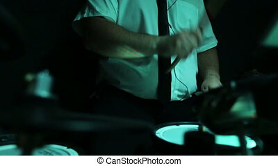Close up of a musician with headphones  playing drums on a stage.
