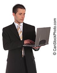 Mobile computing - A handsome businessman using a notebook...