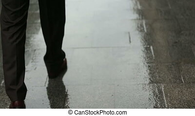 Man walks on rainy London streets close up