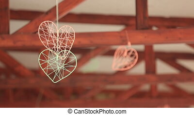 Two cute hand made hearts  hanging on ceiling. Wedding decorations