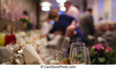 Waiters serving table in a wedding ceremony for guests and a...