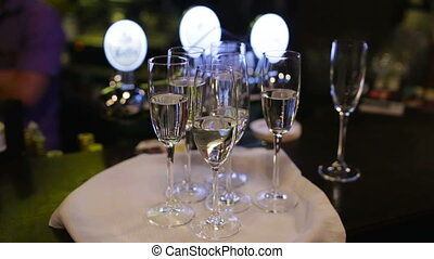 Six champagne glasses on a waiters tray.