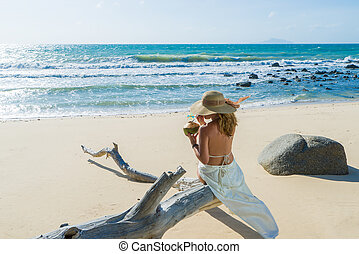 Woman sitting on a tree trunk at the tropical beach holding a fresh coconut drink