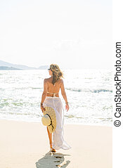 Classy woman holding a straw hat at the beach Vacation Holiday Concept, Girl with Windy Flying Cloth