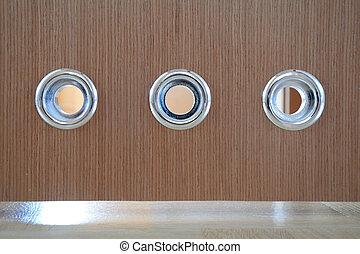Vents in bathroom door. - Round silver vents in brown wooden...