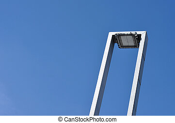 Modern street lamp against blue sky